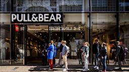 Pelanggan menunggu dalam antrean di depan toko pakaian Pull & Bear yang dibuka kembali di shopping street di Amsterdam, Rabu (28/4/2021). Belanda mulai melonggarkan pembatasan ketat terkait Covid-19, mengakhiri jam malam dan mengizinkan kafe untuk buka di luar ruangan. (REMKO DE WAAL/ANP/AFP)
