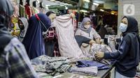 Pedagang melayani pembeli di Pasar Tanah Abang, Jakarta, Minggu (10/10/2021). Dilonggarkannya kebijakan PPKM di Jakarta membuat aktivitas perdagangan di Pasar Tanah Abang kembali bangkit. (Liputan6.com/Faizal Fanani)