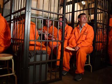 Para pengunjung duduk dalam sel mereka di bar koktail Alcotraz di London Timur, 11 Oktober 2018. Pengunjung harus mengganti pakaian mereka dengan baju tahanan berwarna oranye untuk memasuki bar berkonsep penjara ini. (BEN STANSALL / AFP)