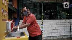 Pengunjung mencuci tangan sebelum memasuki pasar tradisional di Jakarta, Senin (15/6/2020). PD Pasar Jaya mulai hari ini memberlakukan penerapan ganjil genap di pasar tradisional sebagai upaya membatasi jumlah pengunjung selama masa PSBB transisi. (merdeka.com/Iqbal S. Nugroho)
