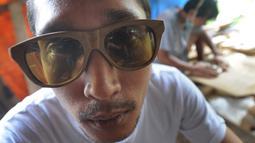 Perajin mencoba kacamata berbahan kayu buatannya di Gang  Madrasah, Pamulang, Tangerang Selatan, Senin (21/1). Dalam sehari, pengrajin mampu menyelesaikan dua buah kacamata yang dijual Rp 200 ribu hingga Rp 500 ribu per buah. (Merdeka.com/Arie Basuki)