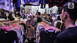 Pedagang mengamati pengunjung memilih pakaian bekas impor di Pasar Senen, Jakarta, Kamis (4/3/2021). Rudi (34) salah satu pedagang mengungkapkan penjualan pakaian bekas impor di Pasar Senen merosot hingga 50 persen sejak awal pandemi COVID-19 melanda Ibu Kota. (merdeka.com/Iqbal S. Nugroho)