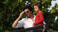 Aktor Bollywood, Shah Rukh Khan menggendong putranya, Abram Khan menyapa para fans yang berkumpul di depan rumahnya pada perayaan Idul Fitri di Mumbai, Rabu (5/6/2019). Ribuan penggemar kerap berkumpul di depan rumah Shah Rukh Khan di momen-momen tertentu. (SUJIT JAISWAL/AFP)