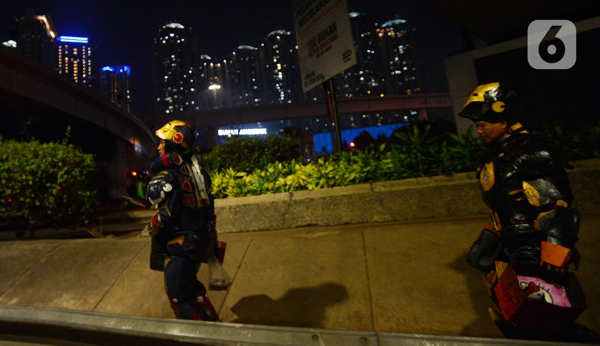 Dua robot berjalan saat menghibur pengendara di kawasan Tomang, Jakarta, Selasa (14/9/2021). Abi (20) dan Nujum (48) mengenakan kostum robot Iron Man untuk mengais rejeki dan menghibur para pengendara dari kemacetan lalu lintas yang dilakukan sejak pandemi COVID-19. (merdeka.com/Imam Buhori)