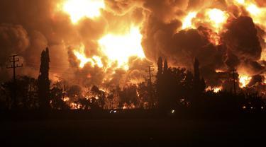 Mobil-mobil melintas sebagai api unggun melalui Kilang Pertamina Balongan di Indramayu, Jawa Barat, Senin (29/3/2021). Ratusan orang dievakuasi dari desa terdekat setelah kebakaran besar terjadi di kilang tersebut. (AP Photo)