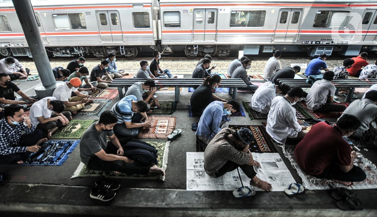 Kereta commuter line melintas dekat jemaah yang tengah salat Jumat di Stasiun Kampung Bandan, Jakarta, Jumat (7/5/2021). Jemaah Masjid Al-Hidayah salat Jumat di Stasiun Kampung Bandan karena keterbatasan lahan, terlebih jumlah meningkat di saat Ramadan. (merdeka.com/Iqbal S. Nugroho)