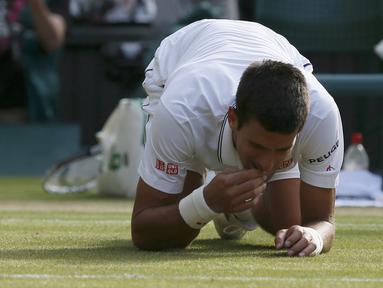 Petenis Novak Djokovic memakan rumput lapangan usai memastikan diri menjadi juara Wimbledon, London, Minggu (6/7/14). (REUTERS/Stefan Wermuth)