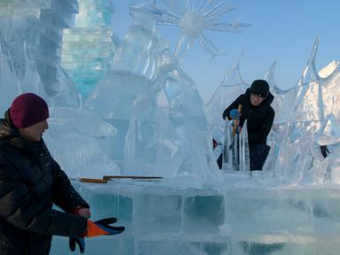 Pemahat es memberikan sentuhan akhir pada patung es di festival Ice and Snow World Harbin, di Harbin, timur laut China, Jumat (3/1/2019).  Festival es terbesar dunia tersebut diadakan untuk menyambut musim dingin yang berlangsung selama satu bulan lebih. (NOEL CELIS/AFP)