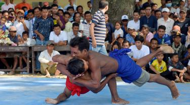 Dua pria bertarung gulat Khmer selama festival Pchum Ben atau festival kematian di desa Vihear Suor, provinsi Kandal (9/10). Warga Kamboja turun dari desa kecil di timur laut ibu kota untuk menyaksikan pertarungan ini. (AFP Photo/Tang Chhin Sothy)