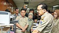 Gubernur DKI Jakarta, Fauzi Bowo memeriksa daftar hadir di komputer saat inspeksi mendadak di Badan Kepegawaian Daerah Provinsi DKI, Jakarta, Kamis (24/9). (Antara)