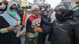 Peserta aksi bersalaman dengan Polisi dari kesatuan Brimob saat gelar doa bersama di depan kantor Bawaslu, Jakarta, Jumat (24/5/2019). Mereka datang untuk mendoakan para demonstran yang meninggal saat aksi 21-22 Mei, pasca hasil penghitungan suara Pemilu 2019. (Liputan6.com/Herman Zakharia)
