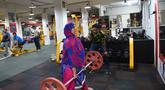 Seorang wanita Muslim India mengangkat beban saat berlatih di gym Ahmedabad Fitness Academy (AFA) di Ahmedabad (10/5/2019). Selama bulan suci Ramadhan, tempat gym ini tetap buka hingga larut malam untuk membiarkan anggota Muslim berolahraga setelah salat. (AFP Photo/Sam Panthaky)