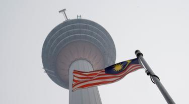 Bendera Malaysia berkibar di bawah Kuala Lumpur Tower saat kabut asap menyelimuti Kuala Lumpur, Malaysia, Rabu (18/9/2019). Badan Meteorologi Klimatologi dan Geofisika (BMKG) mendeteksi sebaran asap akibat kebakaran hutan dan lahan di Sumatra mencapai Malaysia dan Singapura. (AP Photo/Vincent Thian)