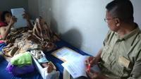Ahmad Mujahidin mengerjakan UN di atas tempat tidur diawasi Maryono (KRJogja.com/Atiek WH)