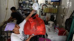 Pekerja menimbang pakaian di toko laundry di Jakarta, Rabu (20/6). Libur lebaran banyak jasa laundry kebanjiran order hingga 100 karena banyaknya para pembatu rumah tangga yang mudik lebaran. (Liputan6.com/Angga Yuniar)