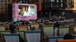 Orang-orang duduk menonton film pada layar lebar saat acara pratinjau bioskop apung di Merchant Square di Kanal Regent, London, Rabu (1/9/2020). Bioskop bernama Openaireini itu memberi dua pilihan tempat duduk kepada penonton, yakni duduk di perahu atau di kursi di tepi kanal. (ISABEL INFANTES/AFP)