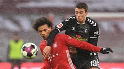 Gelandang Bayern Munich, Leroy Sane (kiri) berebut bola dengan striker Freiburg, Janik Haberer dalam laga lanjutan Liga Jerman 2020/21 pekan ke-16 di Allianz Arena, Minggu (17/1/2021). Bayern Munich menang 2-1 atas Freiburg. (AFP/Christof Stache/Pool)