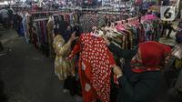 Pembeli memilih pakaian di Pasar Kebayorang Lama, Jakarta, Selasa (29/12/2020). Menteri PPN/Bappenas Suharso Manoarfa menyebut kehilangan daya beli masyarakat akibat pendapatan yang hilang baik langsung dan tak langsung karena pandemi COVID-19 mendekati Rp 1.000 triliun. (Liputan6.com/Johan Tallo)