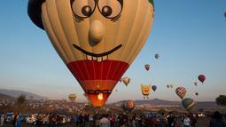 Salah satu peserta yang bersiap menerbangkan balon udaranya saat Festival balon udara di Cajititlan, Meksiko, Minggu (7/5).  Festival balon udara ini menjadi tontonan menarik bagi warga sekitar dan wisatawan. (AFP PHOTO / Hector Guerrero)