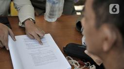 Petugas menunjukkan sanksi hukuman pelanggar PSBB yang tertuang dalam undang-undang di area Pasar Kramat Jati, Jakarta, Rabu (17/6/2020). (merdeka.com/Iqbal S. Nugroho)