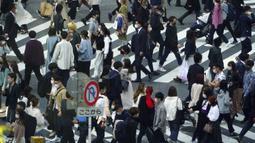 Orang-orang yang mengenakan masker pelindung untuk membantu mengekang penyebaran virus corona COVID-19 menyeberang jalan di Distrik Shibuya, Tokyo, Jepang, Rabu (7/4/2021). Tokyo mengonfirmasi lebih dari 550 kasus COVID-19 baru pada 7 April 2021. (AP Photo/Eugene Hoshiko)