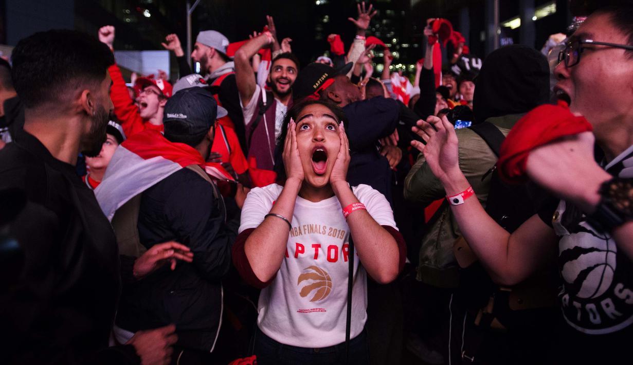 Ekspresi penggemar saat merayakan kesuksesan Toronto Raptors menjuarai NBA 2018-2019, Jumat (14/6/2019) pagi WIB. Kemenangan tersebut memicu kegemparan di Kanada. (Nathan Denette/The Canadian Press via AP)
