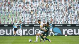Penyerang Borussia Monchengladbach, Lars Stindl, berebut bola dengan gelandang Wolfsburg, Renato Steffen, pada laga lanjutan Bundesliga di Borussia Park Stadium, Rabu (17/6/2020) dini hari WIB. Monchengladbach menang telak 3-0 atas Wolfsburg.(AFP/Thilo Schmuelgen/pool)