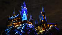 Cahaya warna-warni menghiasi kastil Dunia Harry Potter dihiasi cahaya biru di Universal Studios Hollywood, Universal City (16/11). Pertunjukan ini bertemakan 'The Magic of Christmas at Hogwarts Castle'. (AFP Photo/Chris Delmas)