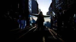 Seorang wanita memegang bendera Argentina selama protes terhadap berbagai masalah termasuk kebijakan ekonomi pemerintah dan kebijakan negara untuk memerangi penyebaran COVID-19 di Buenos Aires, Argentina, Senin (12/10/2020). (AP Photo/Natacha Pisarenko )