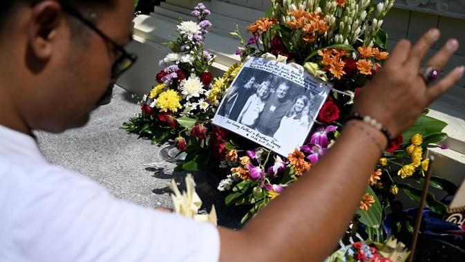 Seorang pria berdoa di Monumen Bom Bali, Kuta, dekat Denpasar pada Sabtu (12/10/2019). MeMperingati 18 tahun peristiwa bom Bali yang terjadi pada 12 Oktober 2002, wisatawan dan kerabat korban mengunjungi tugu peringatan untuk berdoa dan tabur bunga. (SONNY TUMBELAKA / AFP)