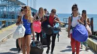 Turis asing yang dievakuasi dari Gili Trawangan tiba di Pelabuhan Bangsal, Lombok Utara, NTB, Selasa (7/8). Gempa 7 skala Richter mengguncang Lombok dan menewaskan 91 orang. (ADEK BERRY/AFP)