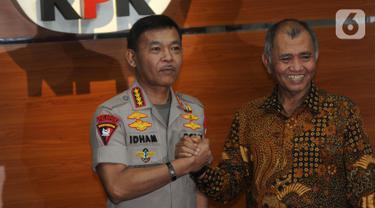 Pimpinan KPK Agus Rahardjo (kanan) dan Kapolri Jenderal Idham Azis (kiri) salam komando usai menggelar pertemuan tertutup di Gedung KPK, Jakarta, Senin (4/11/2019). Pertemuan membahas sinkronisasi antara Kepolisian dengan KPK. (merdeka.com/Dwi Narwoko)