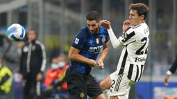 Pemain Juventus Federico Chiesa (kanan) berebut bola dengan pemain Inter Milan Roberto Gagliardini pada pertandingan Serie A di Stadion San Siro, Milan, Italia, Minggu (24/10/2021). Pertandingan berakhir dengan skor 1-1. (AP Photo/Luca Bruno)