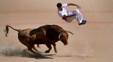 Seorang recortador melompati serudukan banteng selama Festival San Fermin di Pamplona, Spanyol, Sabtu (9/7).Festival yang sempat mengalami kecaman dari aktivis hewan ini tetap menjadi tontonan menarik warga Spanyol. (REUTERS / Vincent West)