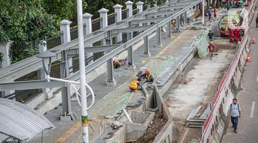 Sejumlah pekerja menyelesaikan pembangunan selter di kawasan Stasiun Palmerah, Jakarta, Selasa (2/2/2021). Penataan kawasan Stasiun Palmerah mencakup pembangunan selter untuk bus, angkot, dan ojek online. (Liputan6.com/Faizal Fanani)