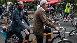 Imam Osman Oers (depan) dan Rabbi Akiva Weingarten mengayuh sepeda tandem sebagai kampanye lintas agama di  Berlin, 24 Juni 2018. Sekitar 25 orang Yahudi dan Muslim yang ikut dalam aksi lintas agama itu diantaranya rabbi dan imam. (AFP/John MACDOUGALL)