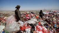 Seorang bocah laki-laki berdiri di antara tumpukan sampah di sebuah tempat pembuangan akhir (TPA) di pinggiran Sanaa, Yaman, Rabu (16/11). Setiap hari para bocah di daerah tersebut mengumpulkan sampah untuk didaur ulang. (REUTERS/Mohamed al-Sayaghi)