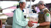 Pelaksana Tugas Wali Kota Bengkulu Dedy Wahyudi menyerahkan bantuan beras kepada warga. (LIputan6.com/Yuliardi Hardjo)