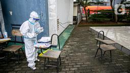 Petugas medis bersiap melakukan swab antigen terhadap pengungsi banjir di Universitas Borobudur, Cipinang Melayu, Jakarta, Minggu (21/2/2021). Swab antigen COVID-19 terhadap pengungsi dilakukan mengingat di pengungsian mereka tidur berhimpitan. (Liputan6.com/Faizal Fanani)