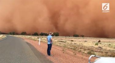 Sebuah keluarga menyaksikan secara langsung badai pasir melanda wilayah pedalaman Australia. Fenomena tersebut membuat warna langit berubah menjadi oranye.