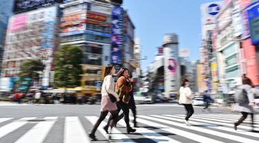 Sejumlah wanita melintasi persimpangan pejalan kaki yang terkenal di distrik Shibuya, Tokyo pada 20 Maret 2019. Persimpangan jalan ini menjadi salah satu persimpangan terbesar dan tersibuk di dunia. (Photo by CHARLY TRIBALLEAU / AFP)
