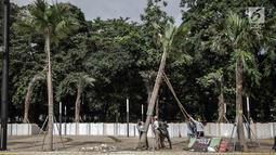 Petugas menumbangkan pohon yang rusak akibat ulah oknum suporter pada Final Piala Presiden 2018 di Stadion Utama GBK, Jakarta, Minggu (18/2). Laga yang dimenangi Persija itu menyisakan sejumlah kerusakan di beberapa area GBK. (Liputan6.com/Faizal Fanani)