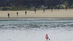 Polisi menggeledah pantai dengan detektor logam jelang KTT G7 di Carbis Bay, Cornwall, Inggris, Senin (7/6/2021). Ribuan polisi tambahan mulai berdatangan di Devon dan Cornwall menjelang KTT G7 pada 11-13 Juni. (Aaron Chown/PA via AP)
