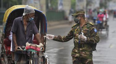 Tentara Bangladesh memeriksa seorang pria yang bepergian dengan becak di sebuah pos pemeriksaan sepanjang jalan Dhaka, Bangladesh, Kamis (1/7/2021). Tentara dan polisi diperintahkan untuk mencegah orang-orang keluar rumah, kecuali untuk keadaan darurat atau membeli kebutuhan pokok. (AFP/Munir Uz zam