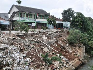 Kondisi tanah longsor di depan Gedung SDIT An-Najah, Kecamatan Cipayung, Kota Depok, Jawa Barat, Selasa (18/2/2020). Longsor di bantaran Kali Baru tersebut terjadi akibat terkikis hujan deras yang melanda pada awal tahun 2020 lalu. (merdeka.com/Iqbal Nugroho)