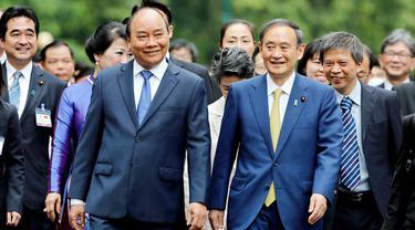 PM Jepang, Yoshihide Suga (kanan tengah) berjalan bersama dengan PM Vietnam, Nguyen Xuan Phuc (kiri depan) setibanya di Istana Kepresidenan, di Hanoi, Vietnam, Senin (19/10/2020). Yoshihide Suga melakukan kunjungan resmi ke Vietnam hingga 20 Oktober 2020.  (AP Photo/Minh Hoang, Pool)