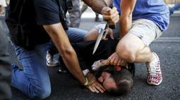Sejumlah orang berusaha mengamankan pelaku penusukan di parade Gay Pride yang digelar di Yerusalem, Kamis (30/7/2015). Akibat penusukan tersebut, enam dari dua korban mengalami luka serius. (REUTERS/Amir Cohen)