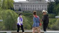 Pejalan kaki dengan masker dan tanpa masker berjalan di dekat Capitol di Olympia, Washington, Selasa (27/4/2021). Warga Amerika Serikat (AS) yang telah menerima vaksin COVID-19 tidak lagi diwajibkan mengenakan masker saat berada di luar ruangan jika tidak ada kerumuman. (AP Photo/Ted S. Warren)