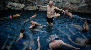 Jose Antonio Aznarez (tengah) bersama yang lain menikmati pemandian air panas alami Sungai Cidaco dengan suhu 52 Celcius saat pagi musim dingin di desa kecil Arnedillo, Spanyol utara, 29 Desember 2018. (AP Photo/Alvaro Barrientos)