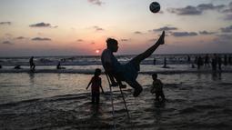 Pemuda Palestina Mohammed Eliwa menendang bola saat bermain di pantai di Kota Gaza (20/9/2019). Eliwa 17 tahun dan Ahmed al-Khoudari 20 tahun kehilangan satu kakinya saat bentrok di perbatasan Israel. (AFP Photo/Mahmud Hams)